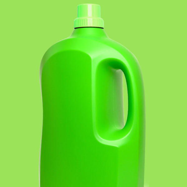 Large bright green plastic bottle with grip hole on green background