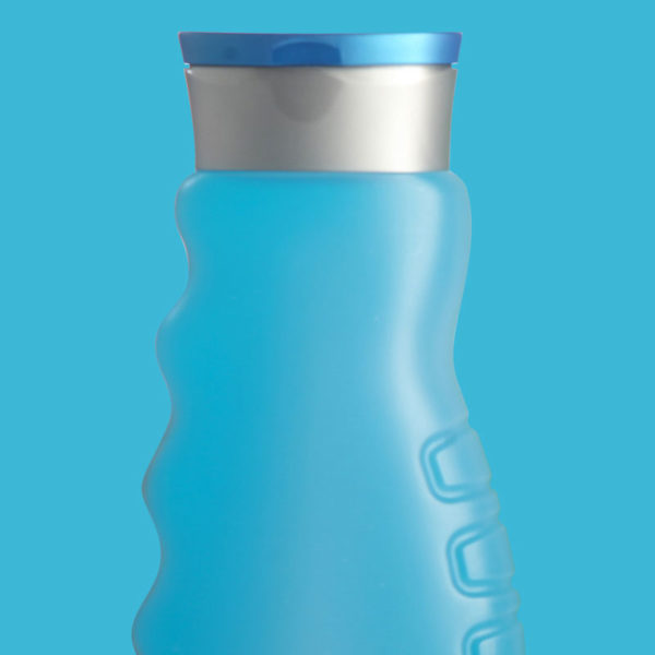 Light blue showergel bottle with grey cap on light blue background